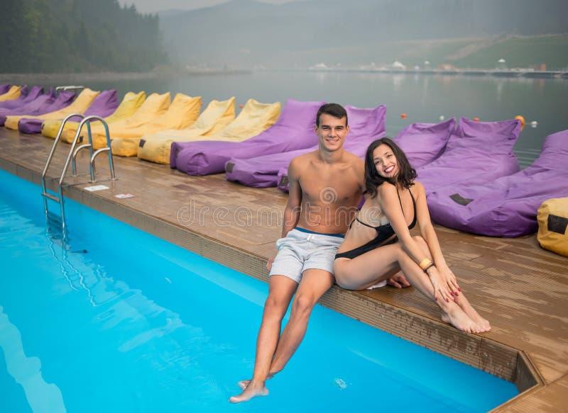Acople o descanso na borda da piscina no recurso no fundo de vistas bonitas das florestas e do lago fotografia de stock