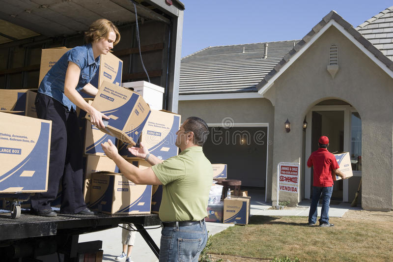 Acople o descarregamento de caixas moventes na casa nova foto de stock
