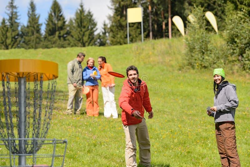 Disco de jogo do frisbee dos pares no parque da primavera imagem de stock royalty free