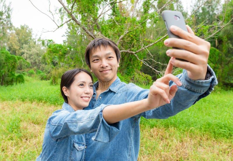 Acople o divertimento que toma fotos da imagem do autorretrato com esperto móvel fotos de stock royalty free