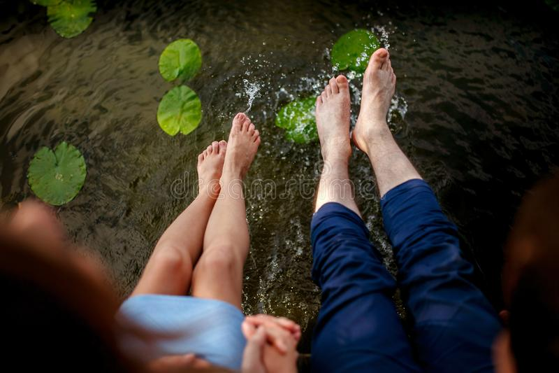 Acople o espirro de seus pés na água no por do sol fotos de stock