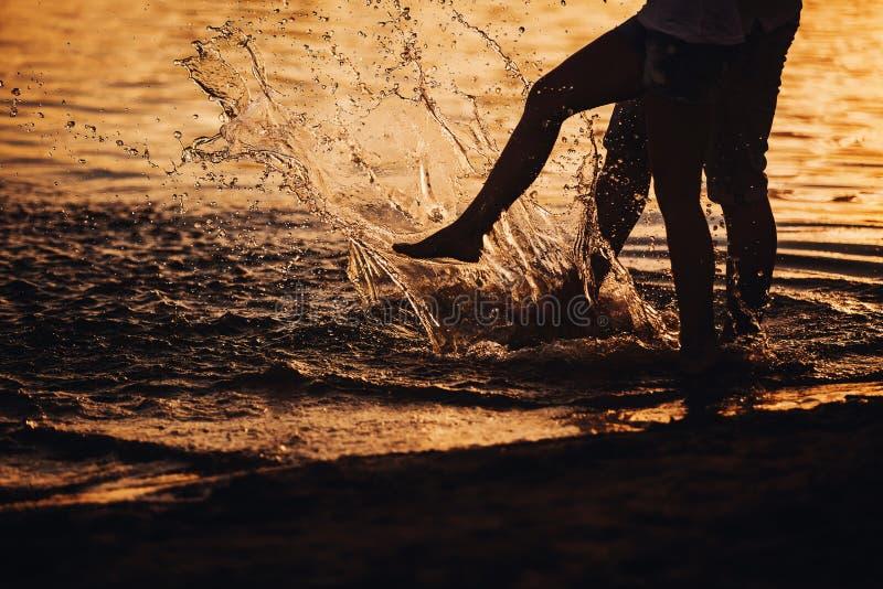 Acople o espirro de seus pés na água no por do sol fotografia de stock royalty free