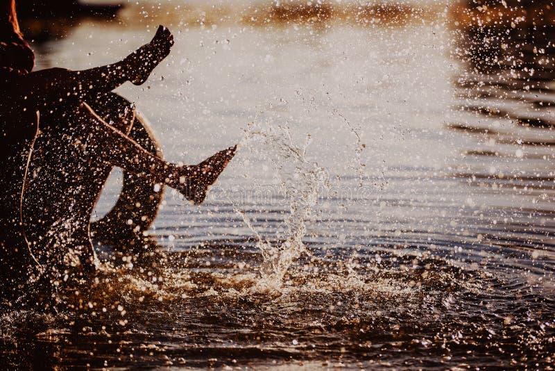 Acople o espirro de seus pés na água no por do sol imagem de stock royalty free