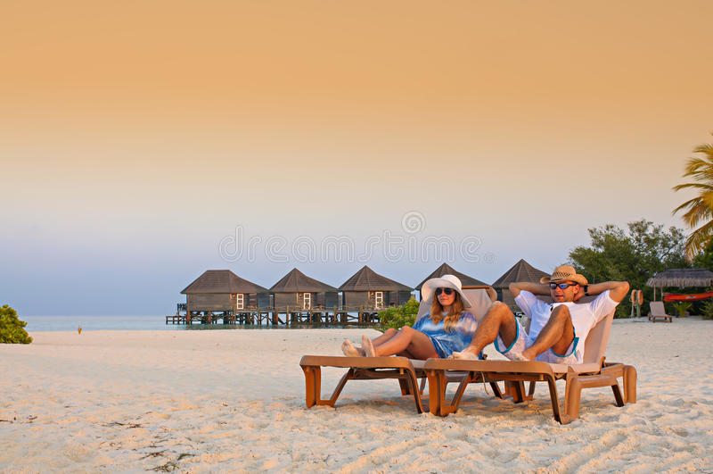 Acople o estabelecimento nos sunbeds que apreciam a praia tropical imagens de stock