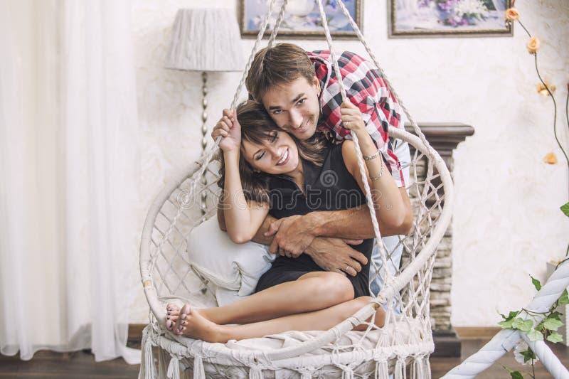 Acople o homem e a mulher em uma cadeira de suspensão que afagam imagens de stock