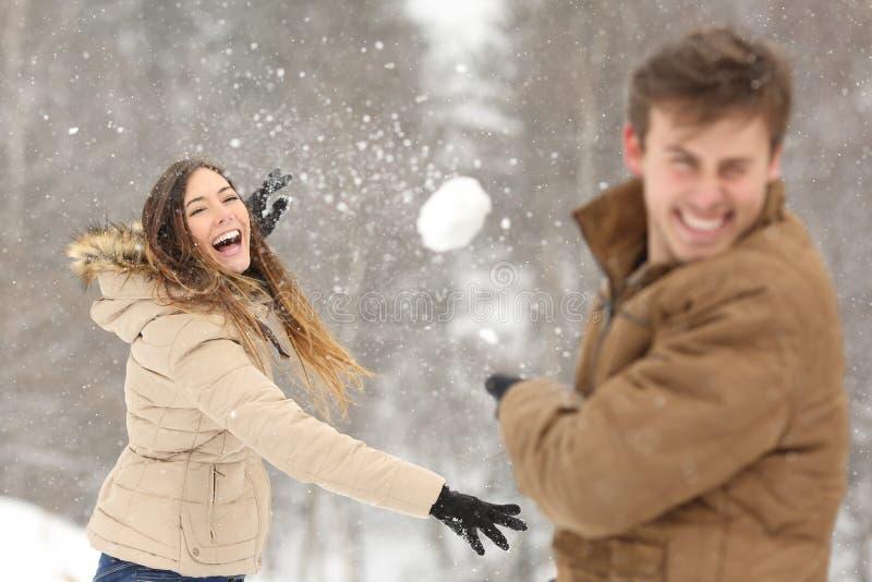 Acople o jogo com a neve e a amiga que jogam uma bola fotografia de stock