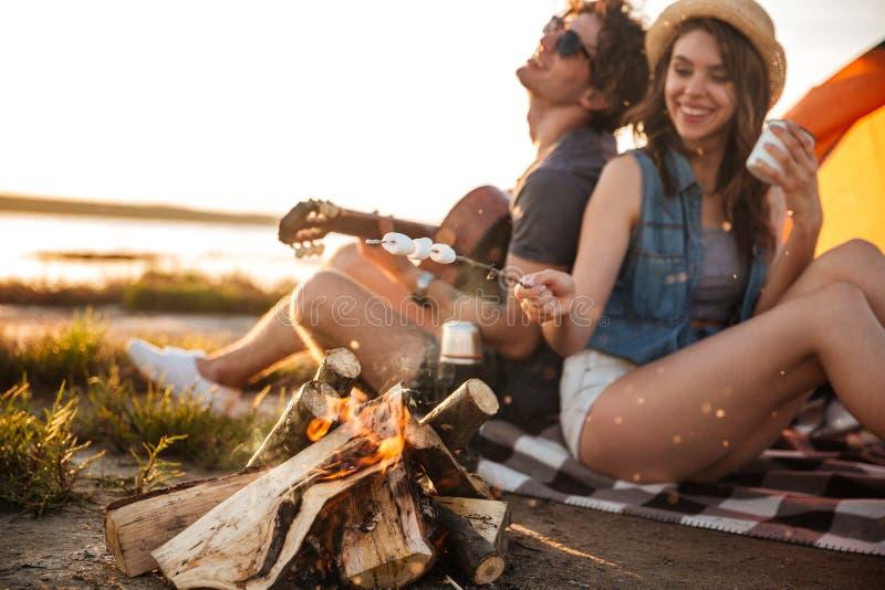 Acople o jogo da guitarra e a fritura de marshmallows na fogueira imagens de stock royalty free