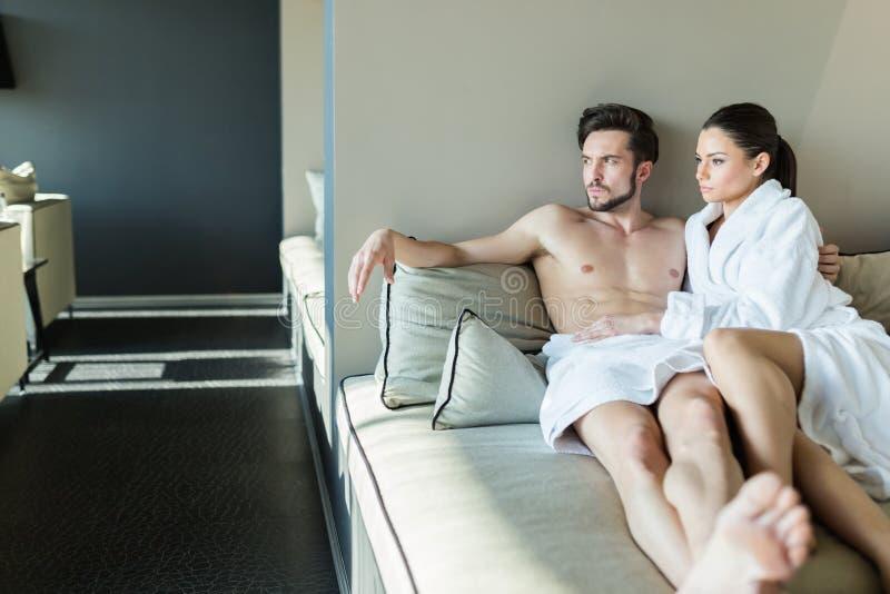 Acople o relaxamento em um centro do bem-estar, colocando em um roubo e em uma toalha fotografia de stock