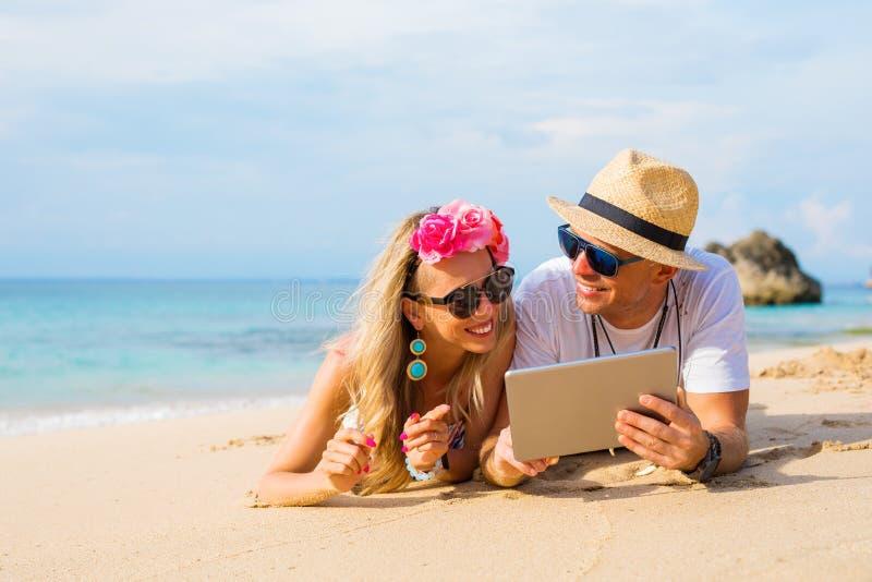 Acople o relaxamento na praia e a vista do tablet pc imagem de stock