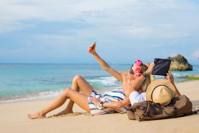 Acople o relaxamento na praia e a vista do tablet pc fotografia de stock royalty free