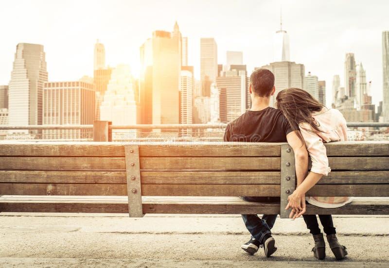 Acople o relaxamento no banco de New York na frente da skyline no sol