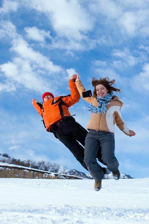Acople o salto sobre o céu azul em montanhas do inverno foto de stock