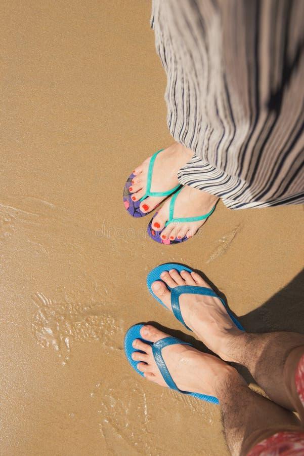 Acople o selfie dos pés em sapatas das sandálias no fundo da areia da praia fotografia de stock