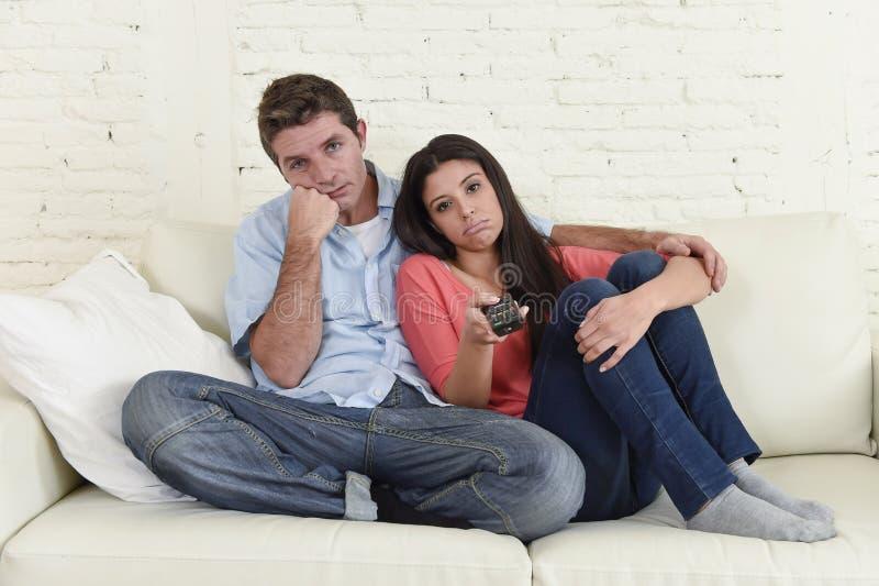Acople o sofá de observação do sofá da televisão junto em casa que olha os canais frustrantes furados do interruptor foto de stock royalty free