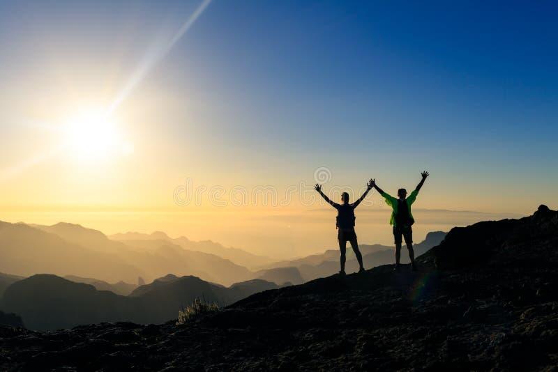 Acople o sucesso dos caminhantes e o conceito da confiança nas montanhas fotografia de stock