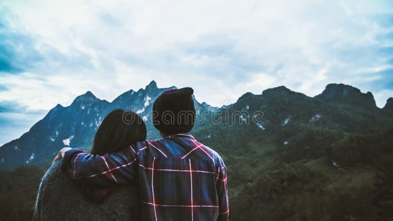 Acople o turista do homem e da mulher no auge da montanha na camisa escocesa e no chapéu negro que caminham no pico de montanha a fotografia de stock