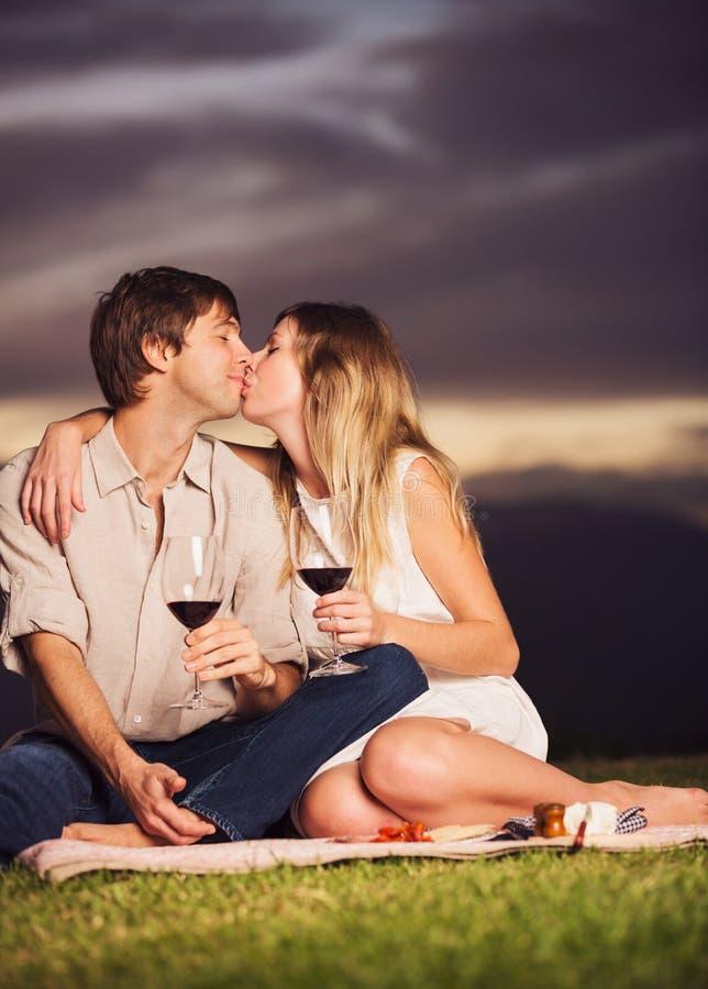 Acople o vidro bebendo do vinho no piquenique romântico do por do sol imagens de stock royalty free