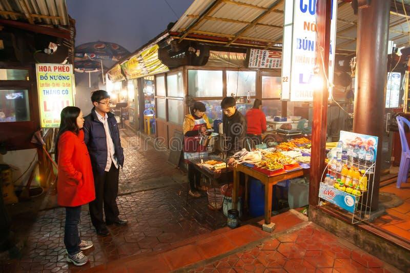 Acople o vietnamita que compra o alimento local no mercado da noite de Pa do Sa, atrações turísticas em Vietname norte foto de stock
