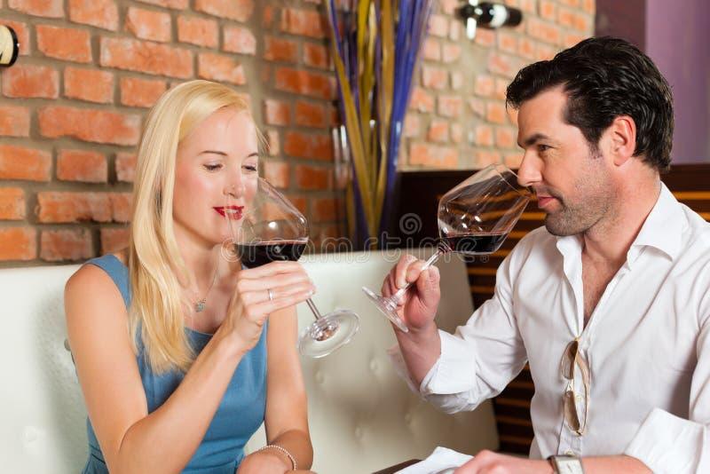 Acople o vinho vermelho bebendo no restaurante ou na barra imagens de stock