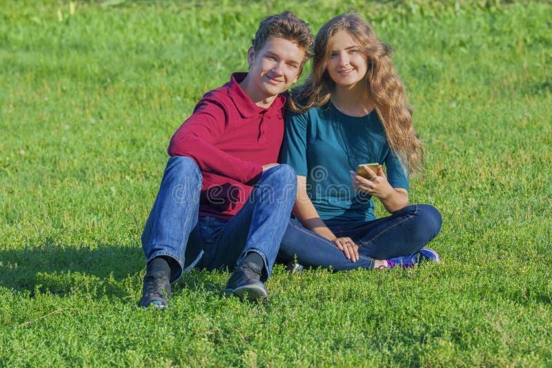 Acople os adolescentes que sentam-se no gramado verde com um smartphone imagens de stock