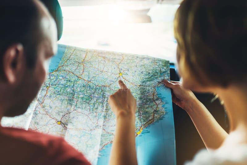 Acople os amigos do moderno que olham e aponte o dedo no mapa da navegação do lugar no auto carro, turista que dois o viajante gu imagens de stock royalty free