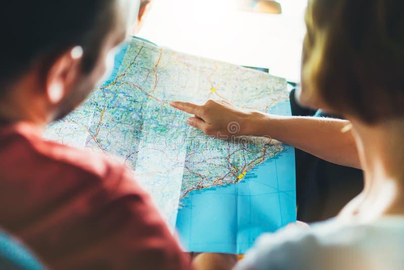Acople os amigos do moderno que olham e aponte o dedo no mapa da navegação do lugar no auto carro, turista que dois o viajante gu fotos de stock