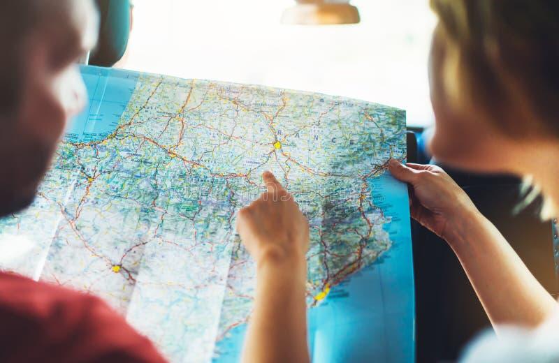 Acople os amigos do moderno que olham e aponte o dedo no mapa da navegação do lugar no auto carro, turista que dois o viajante gu fotos de stock royalty free