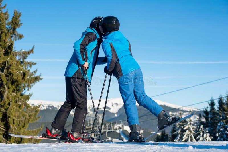 Acople os esquiadores que beijam na parte superior da montanha no dia ensolarado foto de stock royalty free