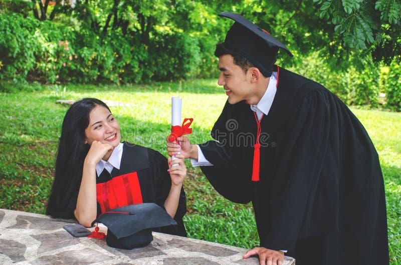 Acople os graduados de sorriso felizes, amigos dos estudantes de mulher nos vestidos da graduação que guardam diplomas e felicite fotos de stock royalty free