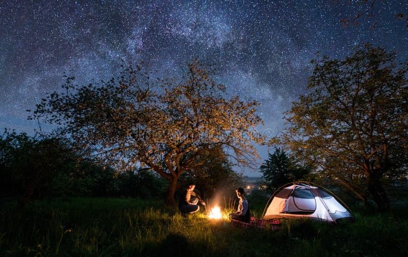 Acople os turistas que sentam-se em uma fogueira perto da barraca sob árvores e do céu noturno completamente das estrelas e da Vi foto de stock