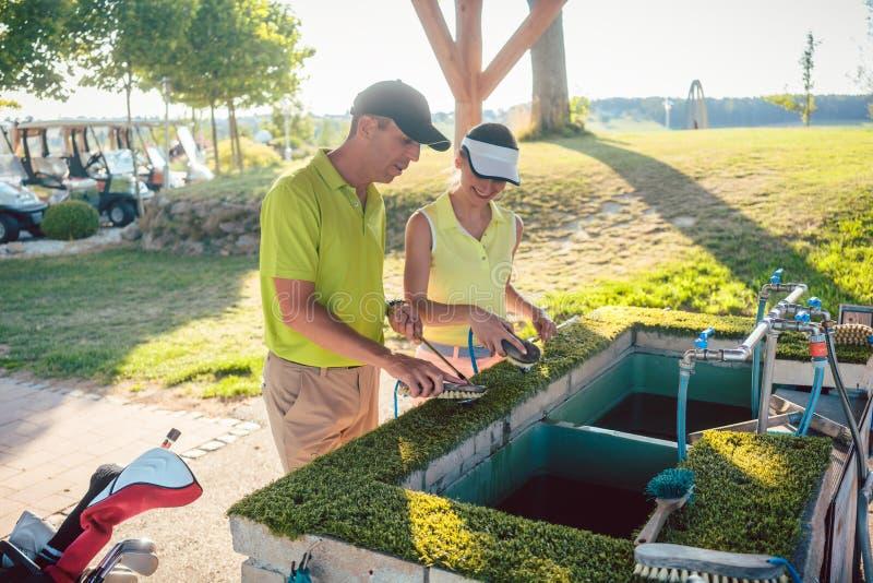 Acople ou dois melhores amigos que limpam seus clubes em um clube de golfe profissional imagem de stock