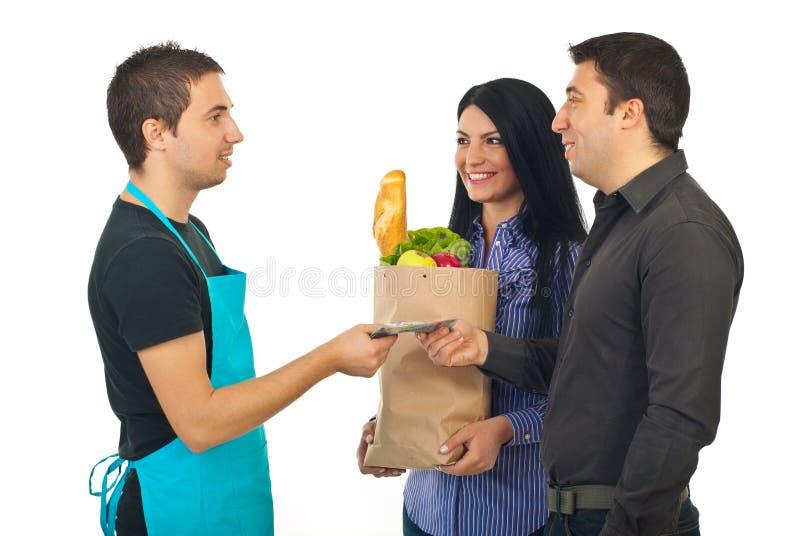 Acople pagar com dinheiro seu alimento no mercado imagens de stock royalty free