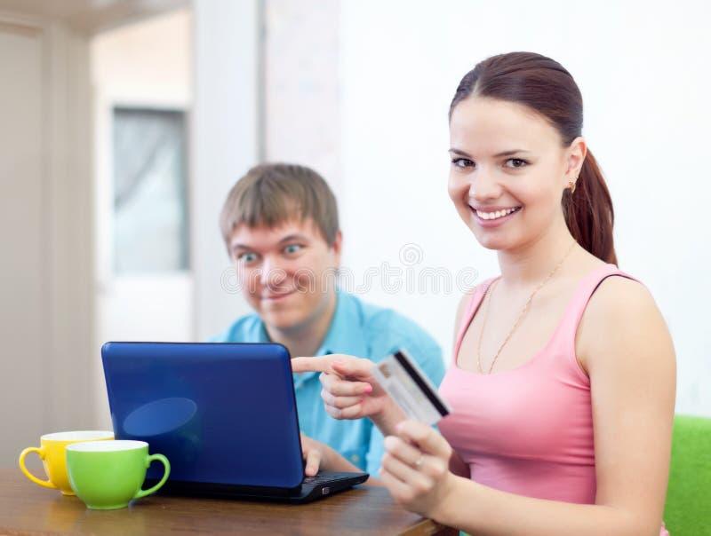Acople pagar pelo cartão de crédito na loja do Internet imagem de stock royalty free