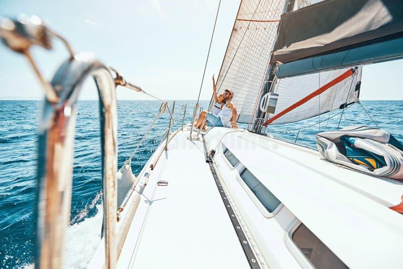 Acople passar o tempo feliz em um iate no mar fotos de stock