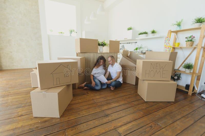 Acople planear sua situação nova da sala de visitas no assoalho família nova que move-se para um apartamento novo e umas caixas l fotografia de stock royalty free