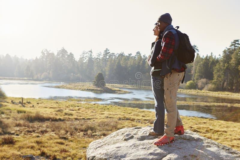 Acople a posição em uma rocha no campo, admirando a vista foto de stock royalty free