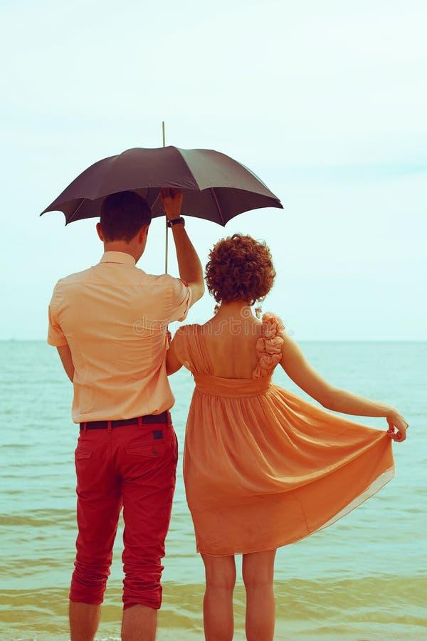 Acople a posição na praia perto da água sob o guarda-chuva imagem de stock royalty free