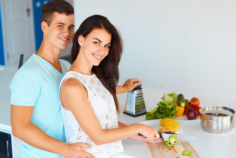 Acople a preparação do jantar e o sorriso na câmera fotos de stock royalty free