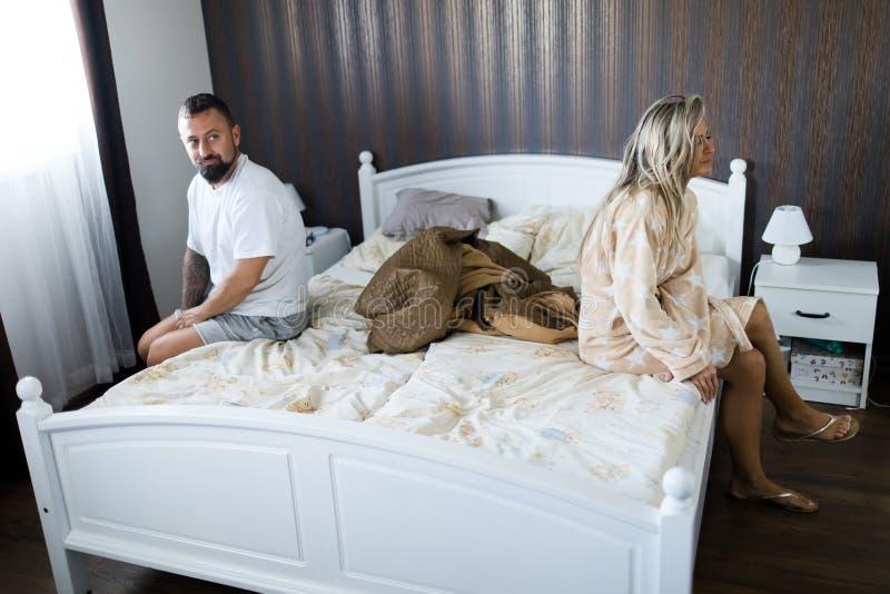 Acople ter a crise na cama Mulher que senta-se na borda da cama imagens de stock royalty free