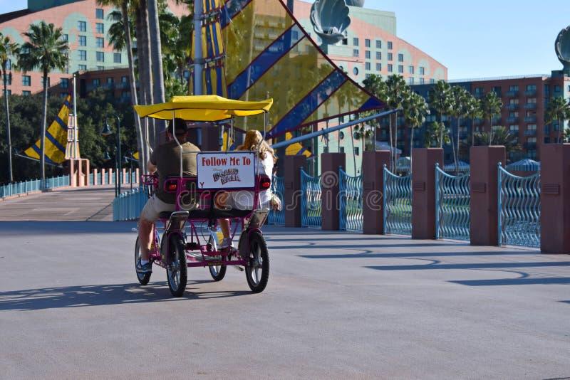 Acople ter o divertimento no passeio pela bicicleta de surrey com vista bonita ao hotel do golfinho no lago Buena V imagens de stock royalty free