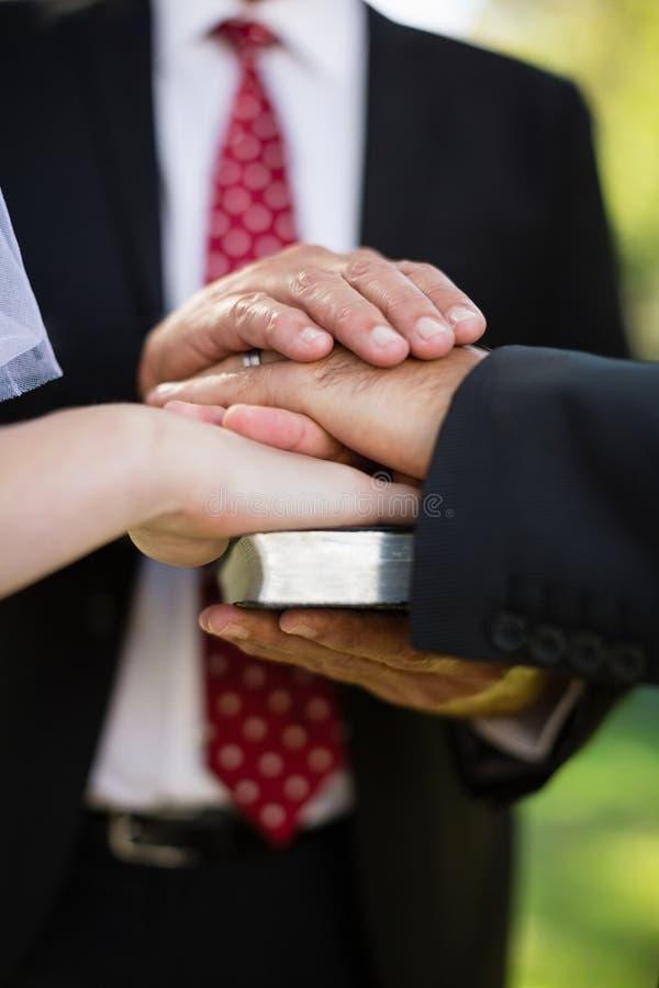 Acople a tomada de um juramento na Bíblia durante o casamento fotografia de stock