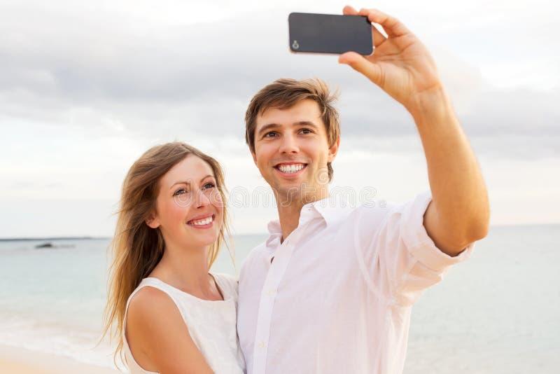 Acople a tomada de um selfie na praia no por do sol foto de stock royalty free