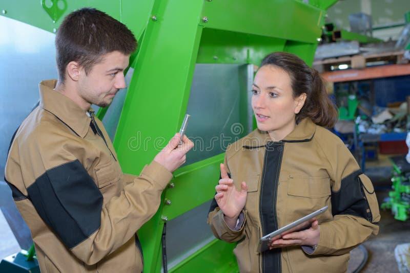 Acople trabalhadores nas combinações perto das máquinas na fábrica imagens de stock royalty free