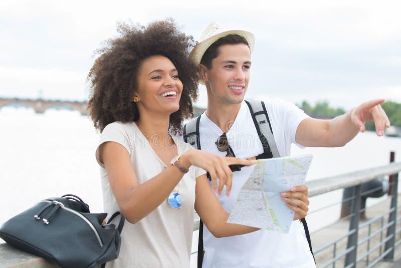 Acople turistas com o mapa perto do rio na cidade foto de stock