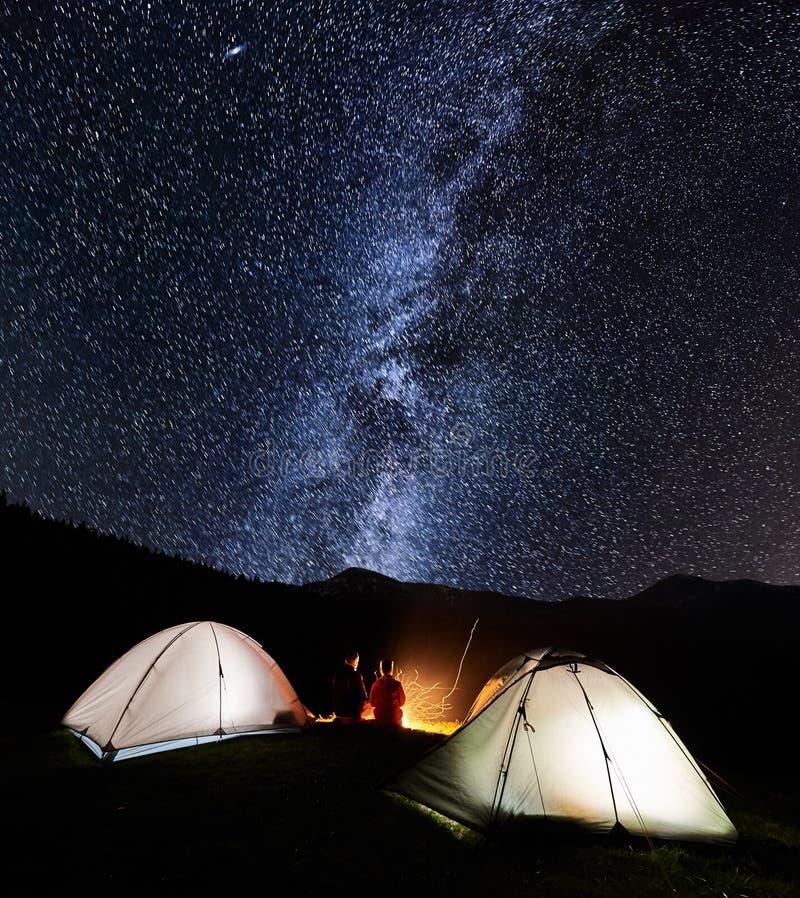 Acople turistas perto da fogueira e das barracas sob o céu noturno completamente das estrelas e da Via Látea imagem de stock royalty free
