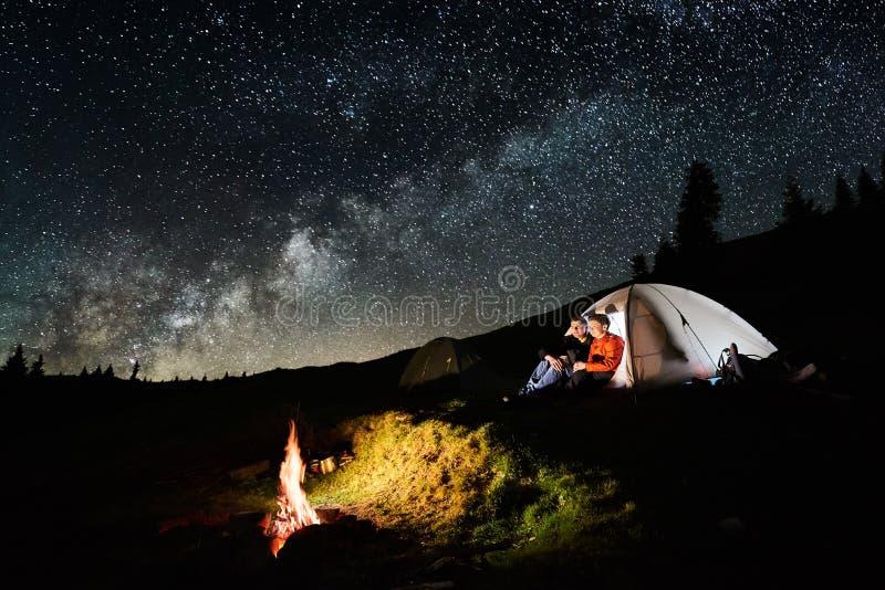 Acople turistas perto da fogueira e das barracas sob o céu noturno completamente das estrelas e da Via Látea foto de stock