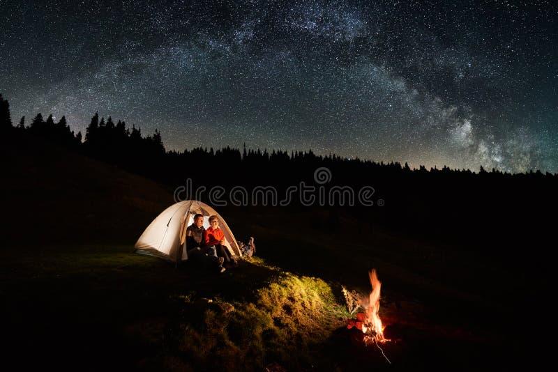 Acople turistas perto da fogueira e das barracas sob o céu noturno completamente das estrelas e da Via Látea fotografia de stock royalty free
