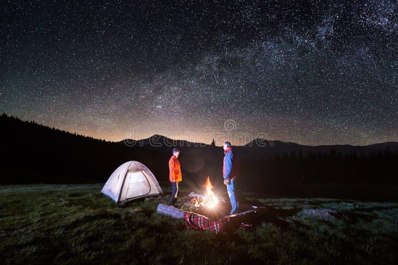 Acople turistas perto da fogueira e das barracas sob o céu noturno completamente das estrelas e da Via Látea fotos de stock royalty free