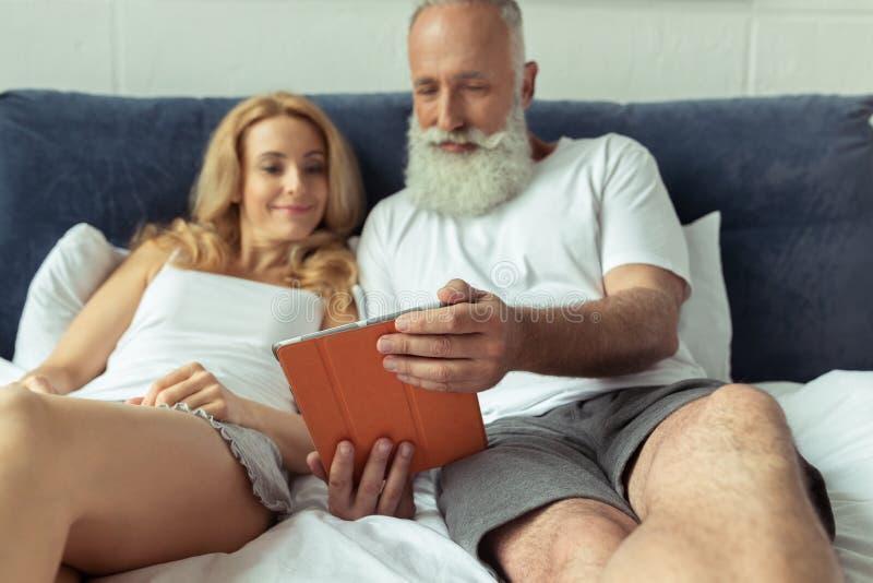 Acople usando a tabuleta digital ao encontrar-se na cama em casa fotografia de stock royalty free