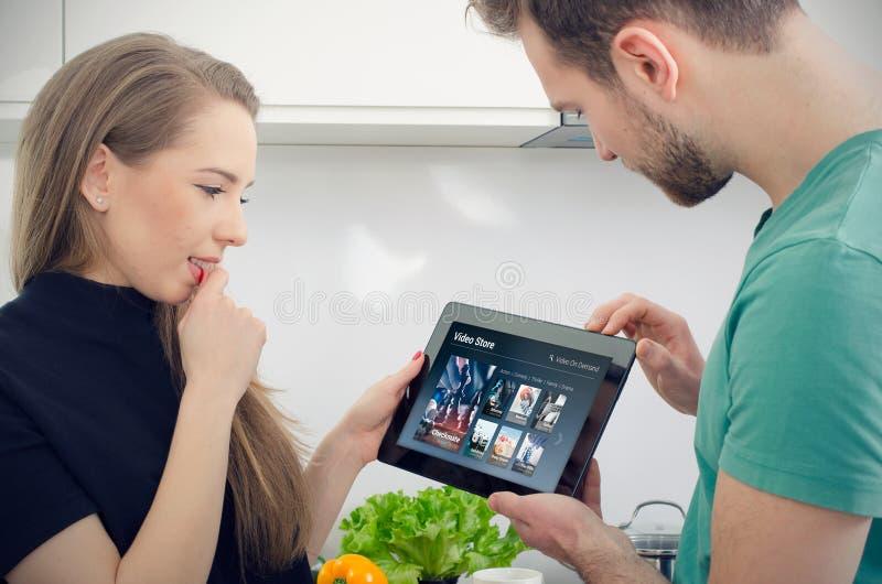 Acople usando a tabuleta digital para o filme de observação no serviço de VOD imagem de stock royalty free